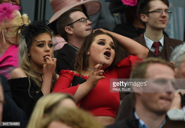 Racegoers react during the third race on Ladies Day of the Grand National Festival horse race meeting at Aintree Racecourse in Liverpool northern...
