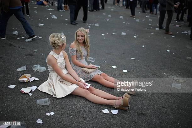 Racegoers relax as they enjoy the atmosphere of Ladies Day at the Aintree Grand National Festival meeting on April 4 2014 in Aintree England Friday...