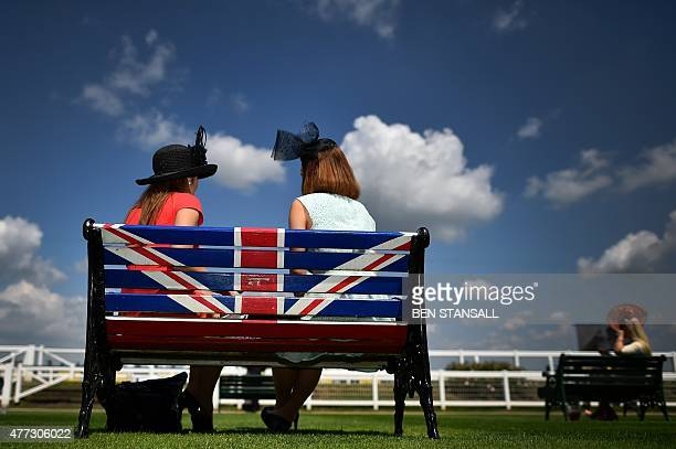 Racegoers relax on a bench displaying the Union Flag on the first day of the annual Royal Ascot horse racing event near Windsor west of London on...