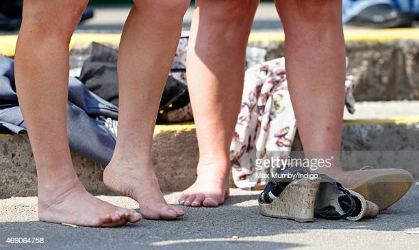 Racegoers remove their shoes as they attend day 1 'Grand Opening Day' of the Crabbie's Grand National Festival at Aintree Racecourse on April 9 2015...