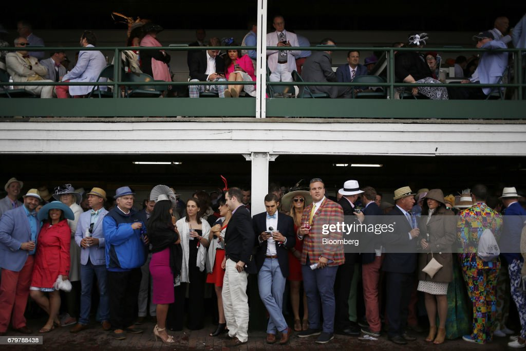 Racegoers seek shelter from the rain beneath a grandstand before the 143rd running of the Kentucky Derby at Churchill Downs in Louisville, Kentucky, U.S., on Saturday, May 6, 2017. The 143rd running of the Kentucky Derby will feature a field of twenty horses with the winner receiving a gold trophy plus an estimated $1.24 million payday. Photographer: Luke Sharrett/Bloomberg via Getty Images