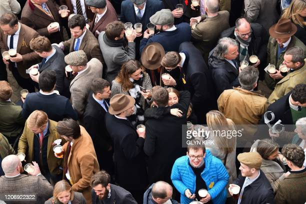 Racegoers share drinks on the final day of the Cheltenham Festival horse racing meeting at Cheltenham Racecourse in Gloucestershire, south-west...