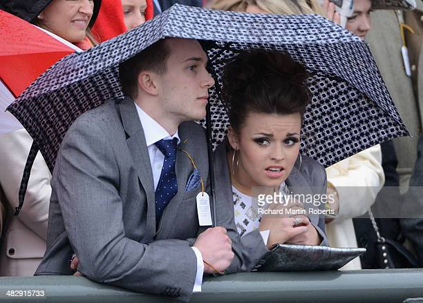 Racegoers shelter from the rain during Day 3 Grand National day of the Aintree races at Aintree Racecourse on April 5 2014 in Liverpool England