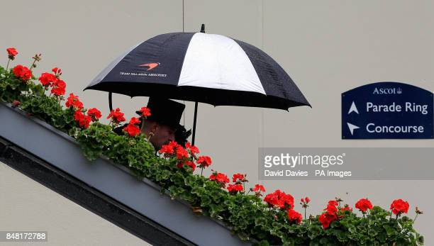 Racegoers shelter from the rain under an umbrella on Ladies Day during day three of the 2012 Royal Ascot meeting at Ascot Racecourse, Berkshire.
