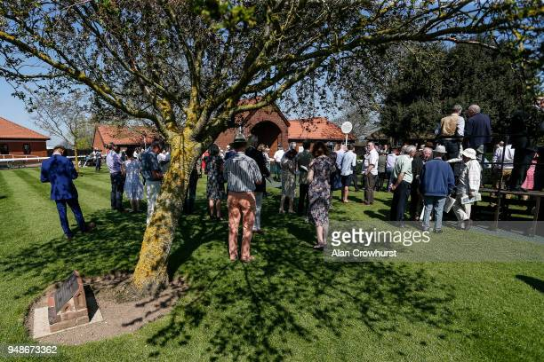 Racegoers shelter from the sun at Newmarket racecourse on April 19 2018 in Newmarket England
