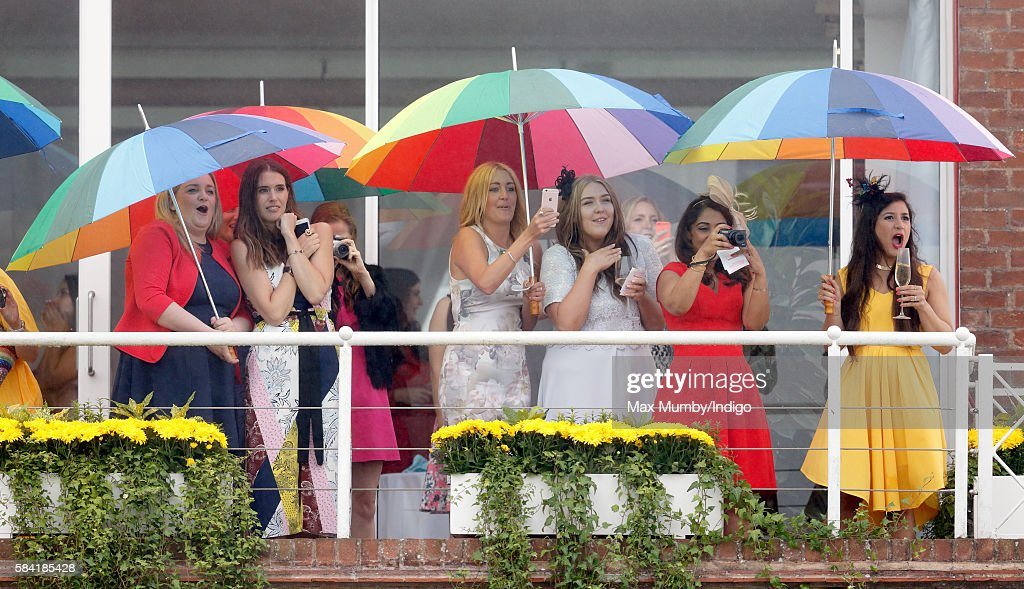 Racegoers shelter under multicoloured umbrellas as they watch the racing on Ladies Day of the Qatar Goodwood Festival at Goodwood Racecourse on July 28, 2016 in Chichester, England.