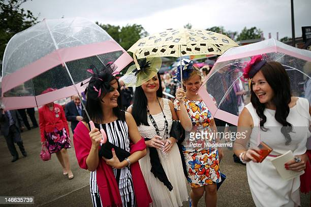 Racegoers shelter under umbrellas during a rain shower at Royal Ascot on Ladies Day on June 21 2012 in Ascot England Ladies Day is traditionally the...
