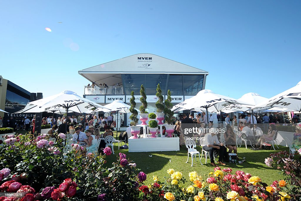 Racegoers sit under umbrellas at the Myer Holdings Ltd. marquee during Melbourne Cup Day at Flemington Racecourse in Melbourne, Australia, on Tuesday, Nov. 5, 2013. The Melbourne Cup, marketed as the race that stops the nation, is Australias premier thoroughbred horse racing event. Photographer: Carla Gottgens/Bloomberg via Getty Images