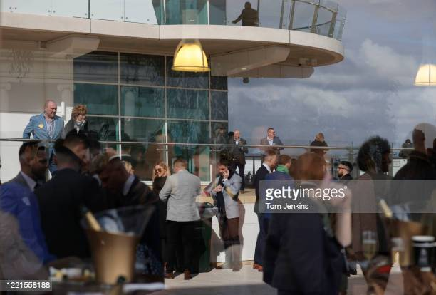 Racegoers socialising before racing during day four of the Cheltenham National Hunt Racing Festival at Cheltenham Racecourse on March 13th 2020 in...
