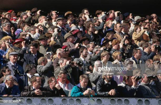 Racegoers, some using binoculars, attending the Seagram Grand National race meeting at the Aintree Racecourse in Aintree, England, 8th April 1989.