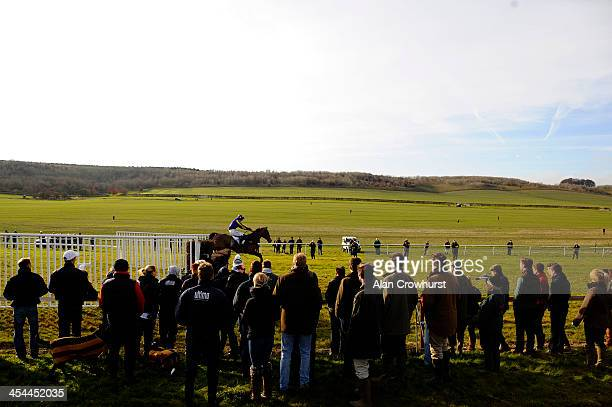 Racegoers stand close to the last fence as the winner clears it during the point to point meeting at Barbury Castle racecourse on December 08 2013 in...