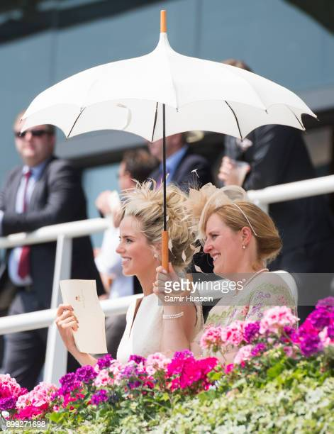 Racegoers stand under an umbrella to hide from the sun as they attend Royal Ascot 2017 at Ascot Racecourse on June 21 2017 in Ascot England