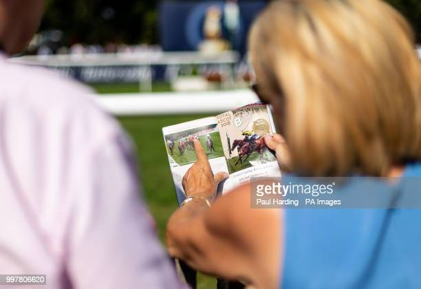 Racegoers study the racecard during day two of The Moet Chandon July Festival at Newmarket Racecourse