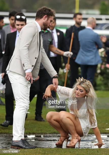Racegoers stumble as they make their way home following Melbourne Cup Day at Flemington Racecourse on November 6 2018 in Melbourne Australia