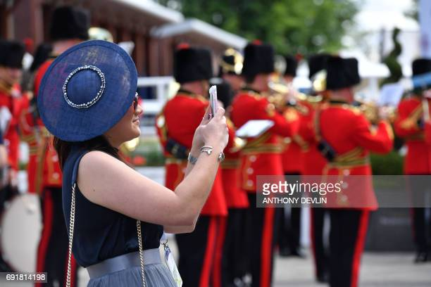 Racegoers take selfies on their mobile phones ahead of the Investec Derby at Epsom Downs Racecourse in Surrey on June 3, 2017. / AFP PHOTO / Anthony...