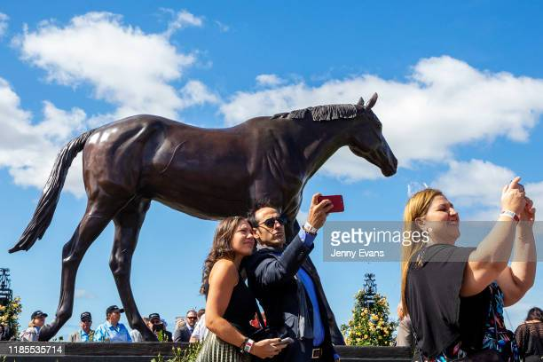 Race-goers take selfies with a statue of Makybe Diva during 2019 Melbourne Cup Day at Flemington Racecourse on November 05, 2019 in Melbourne,...
