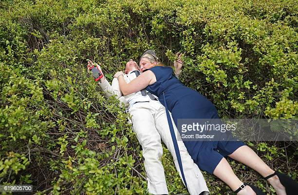Racegoers trip over and fall into a hedge following 2016 Melbourne Cup Day at Flemington Racecourse on November 1 2016 in Melbourne Australia