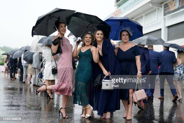 Racegoers use umbrellas to shelter from the rain during day one of the Cazoo Derby Festival at Epsom Racecourse on June 4, 2021 in Epsom, England.