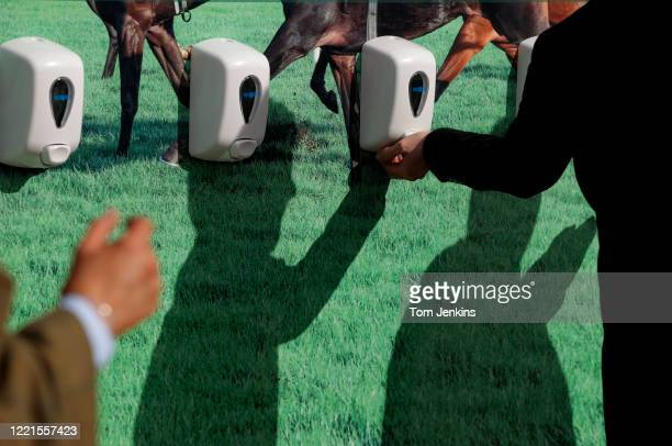 Racegoers using one of the hand sanitizer stations during day four of the Cheltenham National Hunt Racing Festival at Cheltenham Racecourse on March...