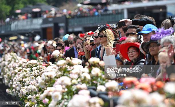 Racegoers wait for the horses to take to the track for the 156th running of the Melbourne Cup at Flemington Racecourse in Melbourne on November 1...