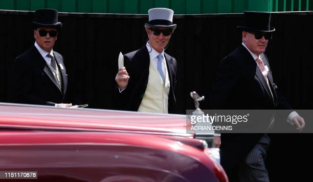 Racegoers walk by a Rolls-Royce car parked in the car park as they attend day four of the Royal Ascot horse racing meet, in Ascot, west of London, on...