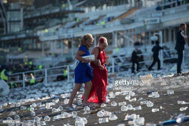 Racegoers walk over discarded plastic cups at the end of Ladies Day of the Grand National Festival horse race meeting at Aintree Racecourse in...