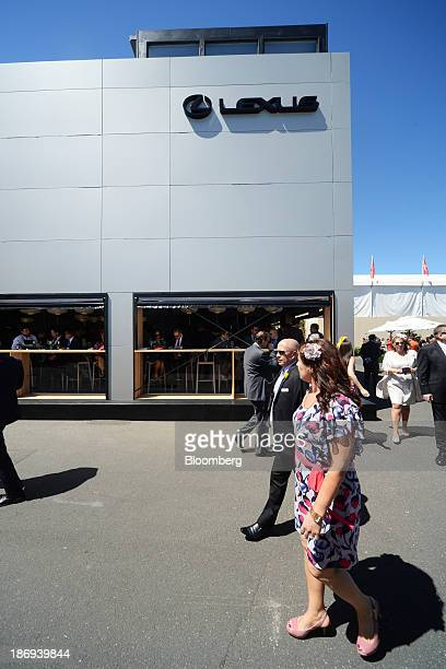 Racegoers walk past a marquee displaying signage for Toyota Motor Corp's Lexus brand in the Birdcage enclosure on Melbourne Cup Day at Flemington...