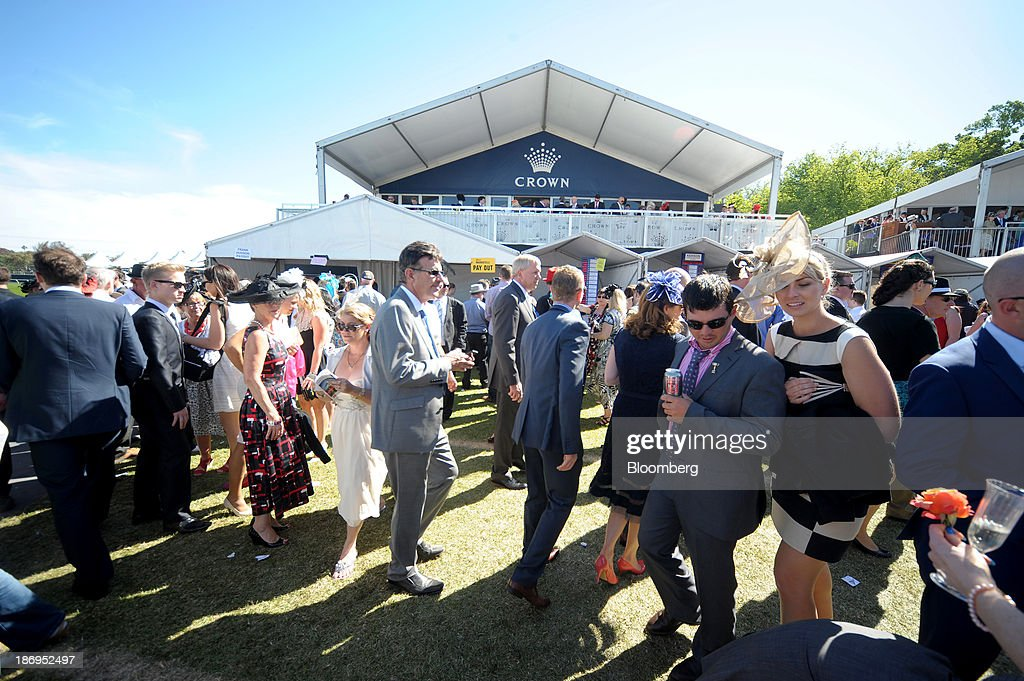 Racegoers walk past the Crown marquee during Melbourne Cup Day at Flemington Racecourse in Melbourne, Australia, on Tuesday, Nov. 5, 2013. The Melbourne Cup, marketed as the race that stops the nation, is Australias premier thoroughbred horse racing event. Photographer: Carla Gottgens/Bloomberg via Getty Images