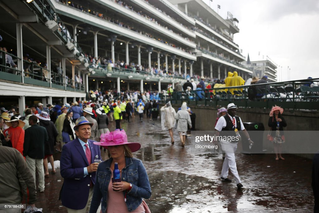 Racegoers walk through a rain storm before the 143rd running of the Kentucky Derby at Churchill Downs in Louisville, Kentucky, U.S., on Saturday, May 6, 2017. The 143rd running of the Kentucky Derby will feature a field of twenty horses with the winner receiving a gold trophy plus an estimated $1.24 million payday. Photographer: Luke Sharrett/Bloomberg via Getty Images