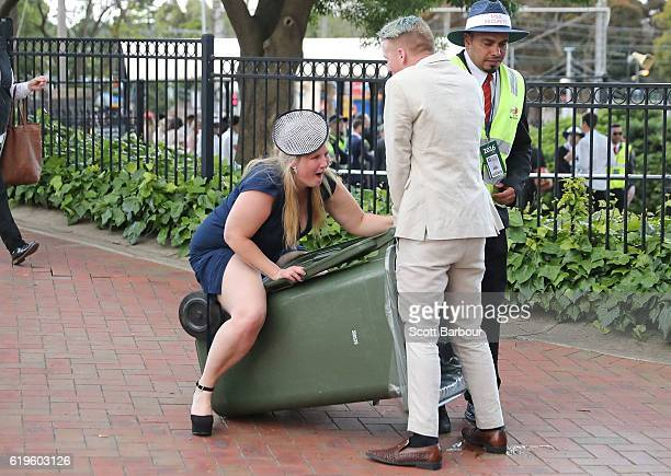A racegoers walks into a rubbish bin following 2016 Melbourne Cup Day at Flemington Racecourse on November 1 2016 in Melbourne Australia