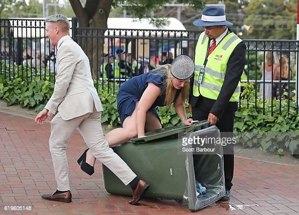 A racegoers walks into a rubbish bin following 2016 Melbourne Cup Day at Flemington Racecourse on November 1 2016 in Melbourne Australia