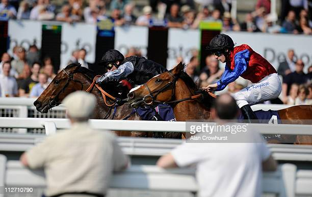 Racegoers watch from the rails as Michael Hills riding Barney Rebel win The Investec Specialist Bank Maiden Stakes at Epsom racecourse on April 20...
