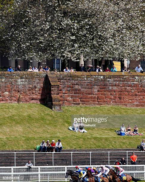 Racegoers watch the action over the Roman wall at Chester racecourse on May 5 2016 in Chester England