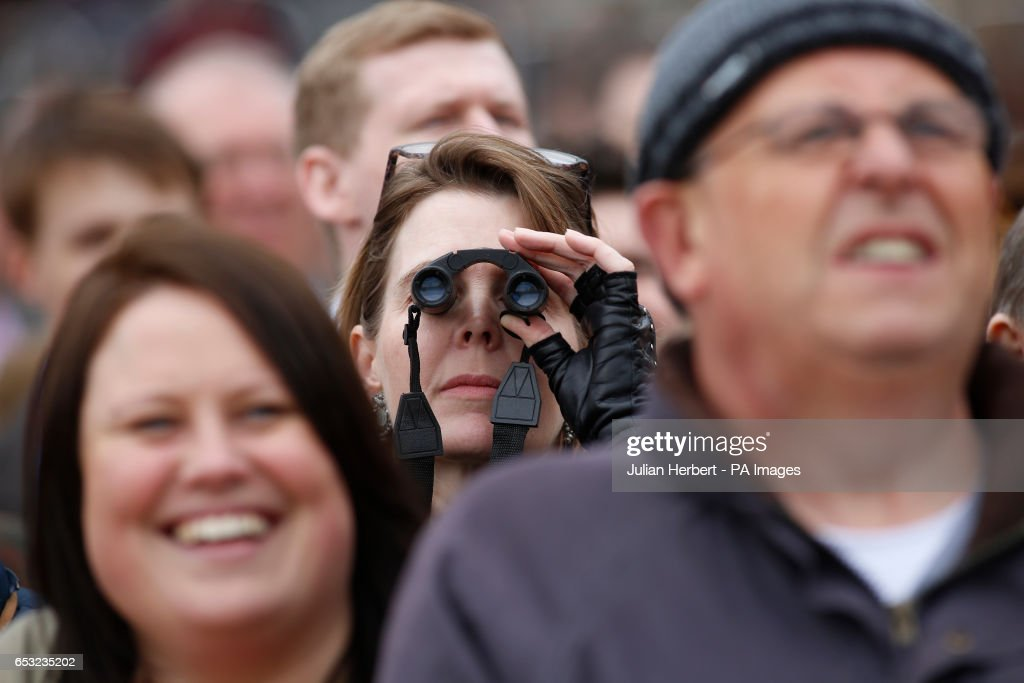 Racegoers watch The Sky Bet Supreme Novices' Hurdle Race run during Champion Day of the 2017 Cheltenham Festival at Cheltenham Racecourse.