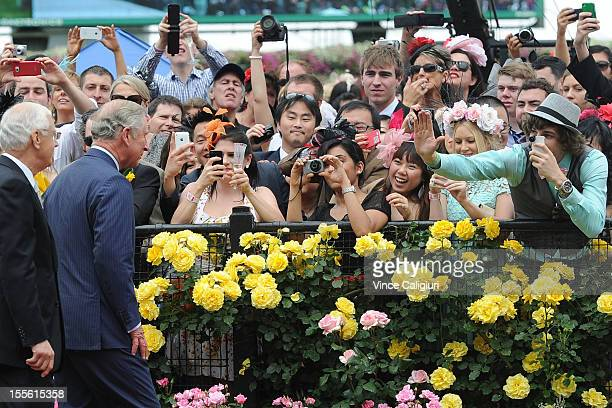 Racegoers wave to Prince Charles Prince of Wales as he arrived in the mounting yard during 2012 Melbourne Cup Day at Flemington Racecourse on...