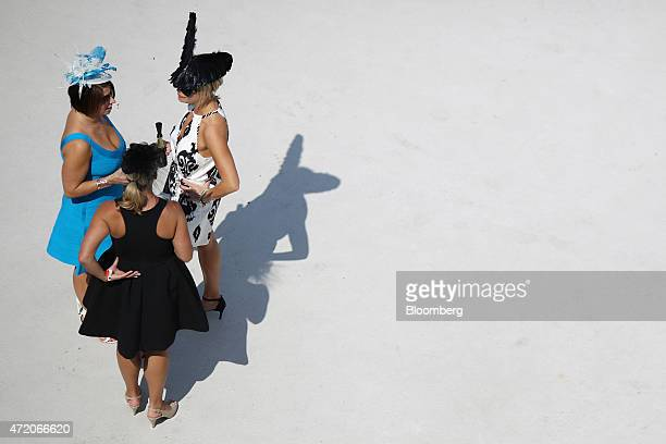 Racegoers wear dresses and derby hats atop the grandstand on the afternoon of the 141st Kentucky Derby at Churchill Downs in Louisville Kentucky US...