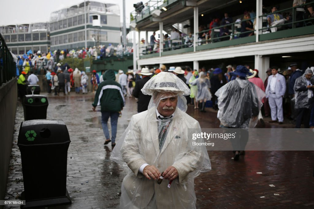 Racegoers wear ponchos during a rain storm on the afternoon of the 143rd running of the Kentucky Derby at Churchill Downs in Louisville, Kentucky, U.S., on Saturday, May 6, 2017. The 143rd running of the Kentucky Derby will feature a field of twenty horses with the winner receiving a gold trophy plus an estimated $1.24 million payday. Photographer: Luke Sharrett/Bloomberg via Getty Images