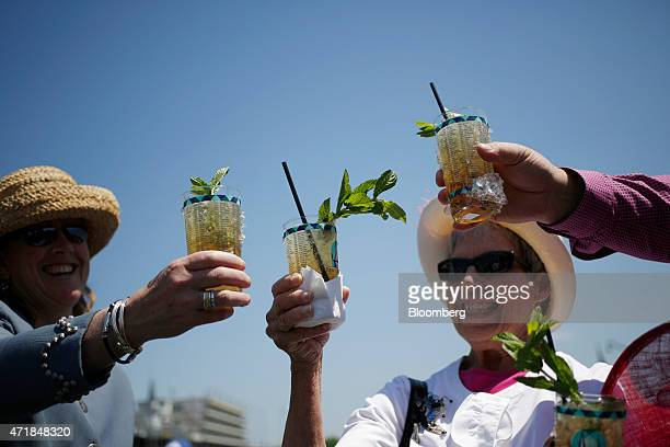 Racegoers who traveled to Churchill Downs from Colorado toast their Mint Julep bourbon cocktails while watching horse races on the eve of the...