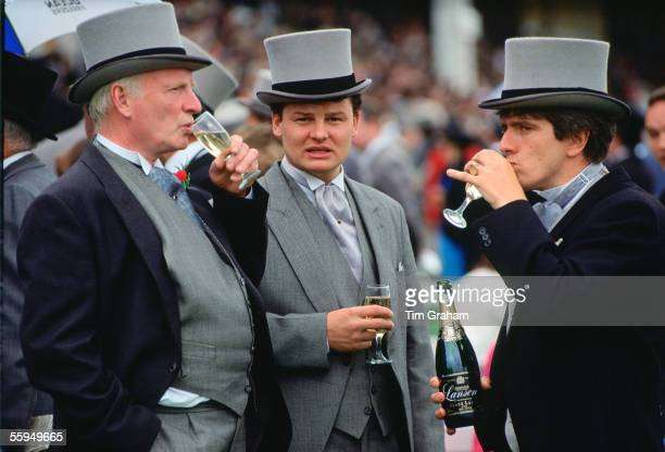Racegoers with bottle of Lanson Black Label champagne at the Epsom Derby Surrey England