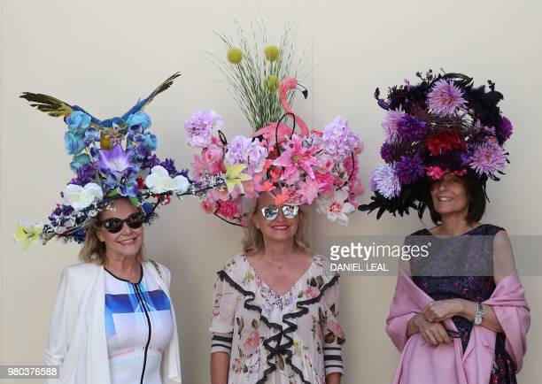 Racegoers with large flower and animalthemed hats pose for a photograph on Ladies Day at the Royal Ascot horse racing meet in Ascot west of London on...