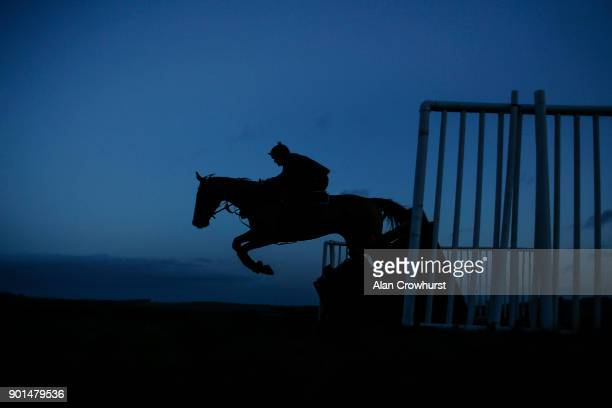 A racehorse schools over the hurdles on the Mandown gallops early morning on January 5 2018 in Lambourn England