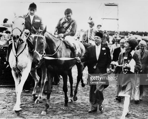 Racehorse, Think Big, ridden by jockey Harry White, is led by part-owner Tunku Abdul Rahman after winning the Melbourne Cup at Flemington race course...