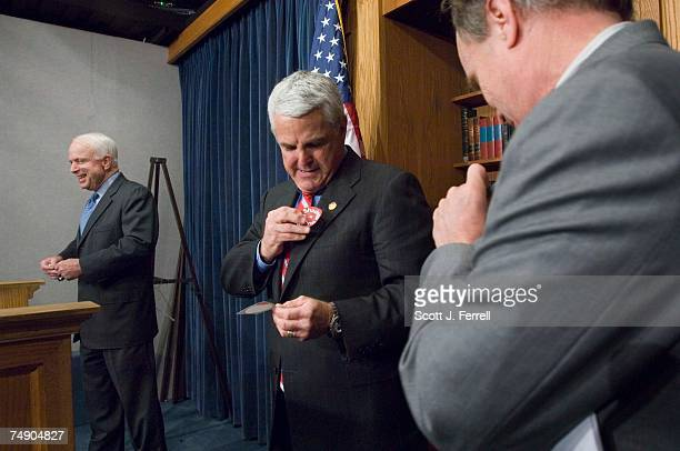 RACEJohn Shadegg RAriz middle puts on a Shadegg = Reform sticker at the beginning of a news conference with supporters Charles Bass RNH right and Sen...