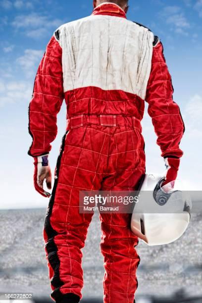 Racer carrying helmet on track