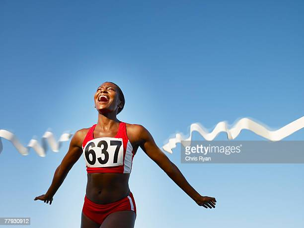 racer crossing the finish line smiling - finish line stock pictures, royalty-free photos & images