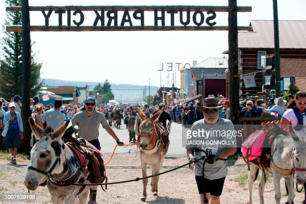 Racers and their burros run through the historical South Park City at the start of the Pack Burro Race during the 70th Annual Burro Days in Fairplay...