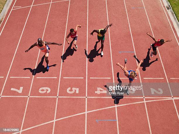 racers at the start line on a track - athletics stock photos and pictures