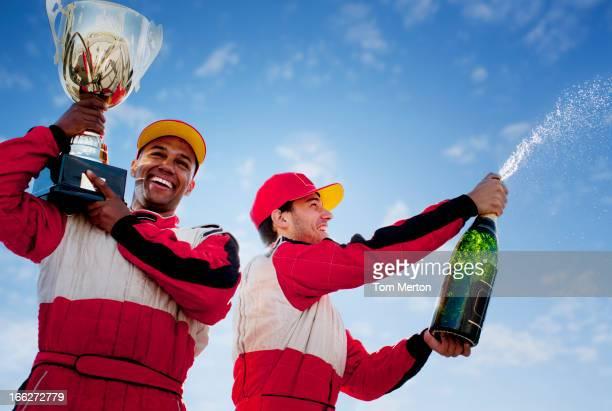 Rennteilnehmer holding trophy und Champagner