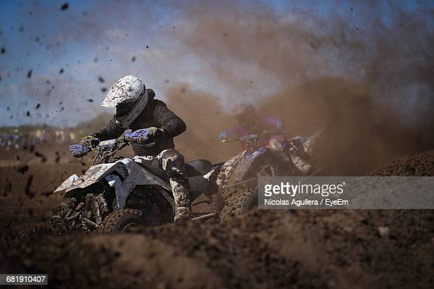 Racers Riding Quadbike In Dirt During Race