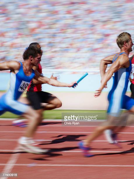 racers running on track with relay baton - relay baton stock photos and pictures